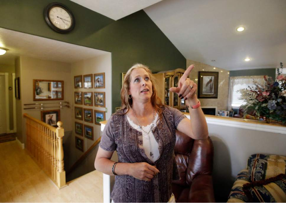 Angie Rice points to a portrait in her home, Tuesday, May 17, 2016, in Mountain Green, Utah. In the year since Utah passed a Mormon church-backed anti-discrimination law protecting gay and transgender people, 22 complaints were filed alleging discrimination in the workplace or in housing. Utah public school teacher Angie Rice, a transgender woman who says the law's protections gave her the courage to come out to administrators and students. (AP Photo/Rick Bowmer)