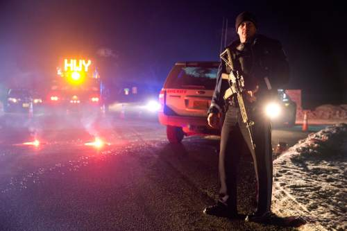 """Sgt. Tom Hutchison stands in front of an Oregon State Police roadblock on Highway 395 between John Day and Burns by Oregon State police officers Tuesday, Jan. 26, 2016. Authorities say shots were fired Tuesday during the arrest of members of an armed group that has occupied a national wildlife refuge in Oregon for more than three weeks. The FBI said authorities arrested Ammon Bundy, 40, his brother Ryan Bundy, 43, Brian Cavalier, 44, Shawna Cox, 59, and Ryan Payne, 32, during a traffic stop on U.S. Highway 395 Tuesday afternoon. Authorities said another person, Joseph Donald O'Shaughnessy, 45, was arrested in Burns. In a statement, the FBI said one individual """"who was a subject of a federal probable cause arrest is deceased.""""   Dave Killen / staff"""