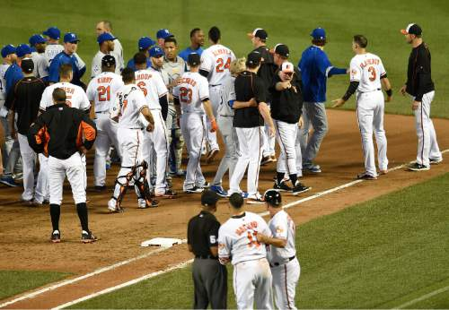 Baltimore Orioles manager Buck Showalter, right, calls to Manny Machado, foreground, after the benches cleared after Kansas City Royals pitcher Yordano Ventura threw a pitch at Machado in the fifth inning of a baseball game, Tuesday, June 7, 2016, in Baltimore. (AP Photo/Gail Burton)