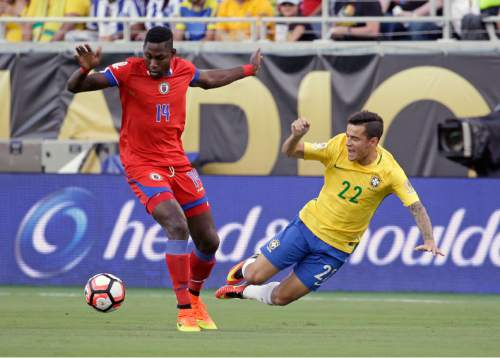 Haiti's James Marcelin (14) and Brazil's Philippe Coutinho (22) collide while going for the ball during the first half of a Copa America group B soccer match Wednesday, June 8, 2016, in Orlando, Fla. (AP Photo/John Raoux)