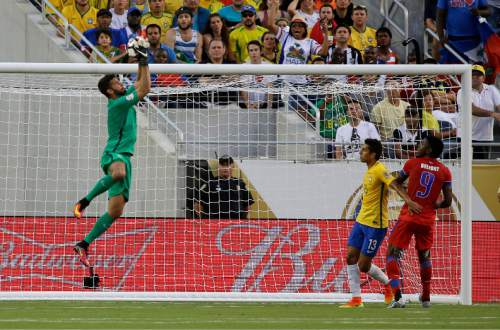 Brazil's Alisson, left, leaps high to stop a shot on goal as Brazil's Marquinhos (13) and Haiti's Kervens Belfort (9) watch during the first half of a Copa America group B soccer match Wednesday, June 8, 2016, in Orlando, Fla. (AP Photo/John Raoux)