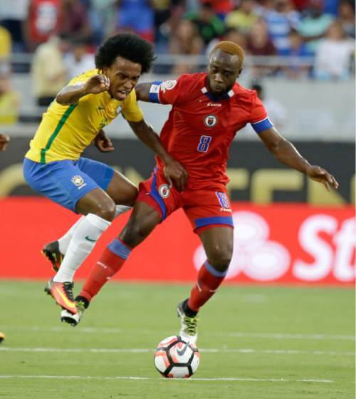 Haiti's Reginal Goreux (8) pushes against Brazil's Willian, left, to get position on the ball during the first half of a Copa America group B soccer match Wednesday, June 8, 2016, in Orlando, Fla. (AP Photo/John Raoux)