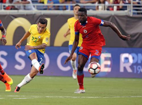Brazil's Philippe Coutinho (22) scores a goal past Haiti's Romain Genevois, right, during the first half of a Copa America group B soccer match Wednesday, June 8, 2016, in Orlando, Fla. (AP Photo/John Raoux)
