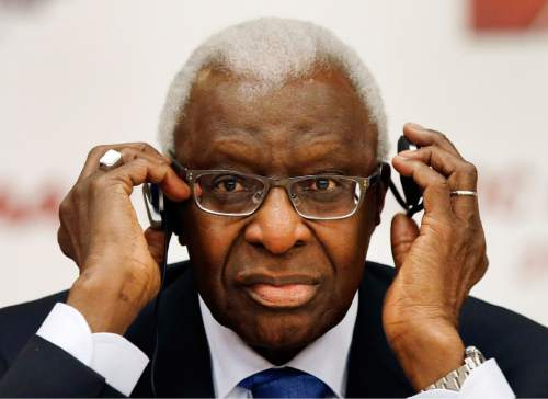 FILE - In this Aug. 21, 2015, file photo, then-IAAF president Lamine Diack adjusts his headphones during a joint IOC and IAAF news conference on the site of the World Athletic Championships in Beijing. Track and field's world governing body on Friday, June 10, 2016 has suspended three staff members in an ethics investigation linked to Russian doping.  The suspension is in connection with an email reportedly sent on July 29, 2013, to then IAAF President Lamine Diack from his son, Papa Massata Diack, who was an IAAF marketing consultant.  (AP Photo/Kin Cheung, File)