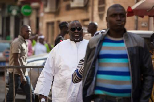 FILE - In this Feb. 17, 2016, file photo, Papa Massata Diack, center, son of former IAAF President Lamine Diack, arrives at the central police station in Dakar, Senegal. Track and field's world governing body on Friday, June 10, 2016 has suspended three staff members in an ethics investigation linked to Russian doping.  The suspension is in connection with an email reportedly sent on July 29, 2013, to then IAAF President Lamine Diack from his son, Papa Massata Diack, who was an IAAF marketing consultant.  (AP Photo/Vincent Tremeau, File)