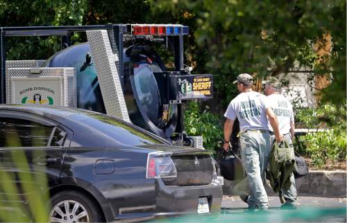 Bomb disposal officers head to check an apartment complex possibly linked to the fatal shooting at an Orlando nightclub, Sunday, June 12, 2016, in Fort Pierce, Fla. (AP Photo/Alan Diaz)