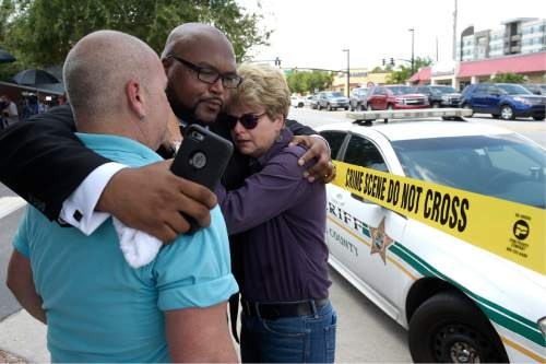 Terry DeCarlo, executive director of the LGBT Center of Central Florida, left, Kelvin Cobaris, pastor of The Impact Church, center, and Orlando City Commissioner Patty Sheehan console each other after a shooting involving multiple fatalities at a nightclub in Orlando, Fla., Sunday, June 12, 2016. (AP Photo/Phelan M. Ebenhack)