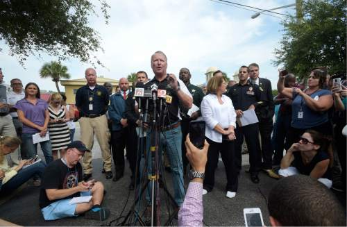 Orlando Mayor Buddy Dyer addresses reporters while flanked by members of law enforcement and community leaders during a news conference after a shooting involving multiple fatalities at a nightclub in Orlando, Fla., Sunday, June 12, 2016. (AP Photo/Phelan M. Ebenhack)