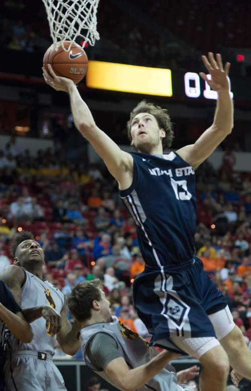Rick Egan  |  The Salt Lake Tribune  Utah State Aggies forward David Collette (13)  goes in for a shot over Wyoming Cowboys guard Riley Grabau (2) in Mountain West Conference Basketball Championship action, Utah State vs. Wyoming, at the Thomas & Mack Center in Las Vegas, Thursday, March 12, 2015.