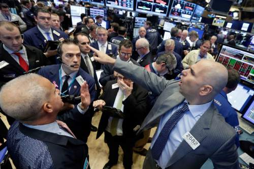 Specialist Philip Finale, right, directs trading in LinkedIn on the floor of the New York Stock Exchange, Monday, June 13, 2016. Microsoft said Monday that it is buying professional networking service site LinkedIn for about $26.2 billion. (AP Photo/Richard Drew)