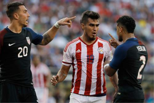 United States' Geoff Cameron, left, and DeAndre Yedlin, right, argue with Paraguay's Dario Lezcano after a tackle during the first half of a Copa America Group A soccer match Saturday, June 11, 2016, in Philadelphia. United States won 1-0. (AP Photo/Matt Slocum)