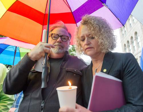 Rick Egan     The Salt Lake Tribune  Russ Isenburg holds the umbrella as Salt Lake City Mayor, Jackie Biskupski holds a candle, at the candlelight vigil in the wake of the mass shooting in Orlando, at the City & County Building, Monday, June 13, 2016.
