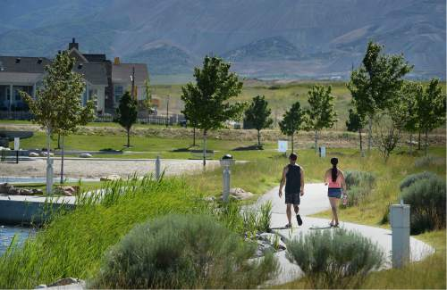 Scott Sommerdorf   |  The Salt Lake Tribune   A couple talks a walk near the pond at the Daybreak community near South Jordan, Friday, June 17, 2016.