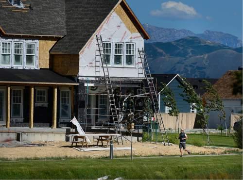 Scott Sommerdorf   |  The Salt Lake Tribune   A man jogs past new construction in the Daybreak community near South Jordan, Friday, June 17, 2016.