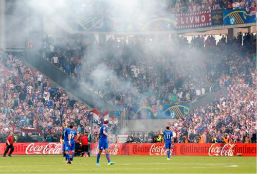 Players stand on the pitch after flares were thrown onto the pitch during the Euro 2016 Group D soccer match between the Czech Republic and Croatia at the Geoffroy Guichard stadium in Saint-Etienne, France, Friday, June 17, 2016 (AP Photo/Laurent Cipriani)