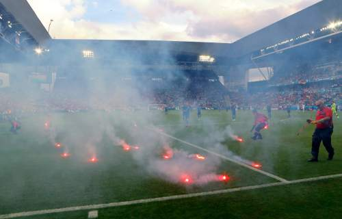 Flares are thrown onto the pitch during the Euro 2016 Group D soccer match between the Czech Republic and Croatia at the Geoffroy Guichard stadium in Saint-Etienne, France, Friday, June 17, 2016. (AP Photo/Darko Bandic)