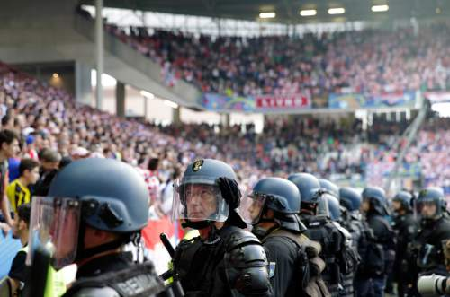 Police officers watch Croatia supporters after flares were thrown on to the pitch during the Euro 2016 Group D soccer match between the Czech Republic and Croatia at the Geoffroy Guichard stadium in Saint-Etienne, France, Friday, June 17, 2016. (AP Photo/Pavel Golovkin)