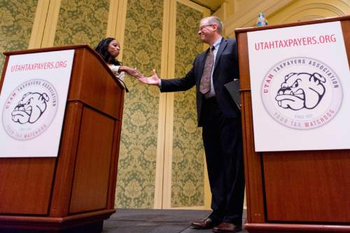 Trent Nelson  |  Tribune file photo  Mia Love and Doug Owens shake hands following their debate at the annual Utah Taxes Now Conference at the Grand America Hotel in Salt Lake City Tuesday, May 20, 2014. A Tribune/Hinckley poll shows that  Owens is ahead of  Love by six points. Political handicappers are calling 2016's race a tossup.