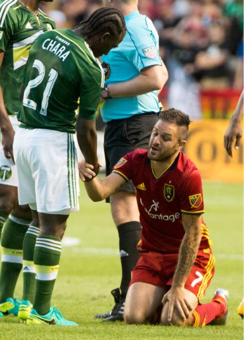 Rick Egan  |  The Salt Lake Tribune  Portland Timbers midfielder Diego Chara (21) helps Real Salt Lake forward Juan Martinez (7) to his feet, after he was given a yellow card, in MLS soccer action, Real Salt Lake vs. Portland Timbers, in Sandy, Friday, June 18, 2016.