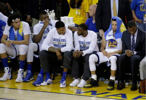 Golden State Warriors guard Stephen Curry (30) and teammates sit on the bench during the second half of Game 7 of basketball's NBA Finals between the Warriors and the Cleveland Cavaliers in Oakland, Calif., Sunday, June 19, 2016. The Cavaliers won 93-89 to win the series. (AP Photo/Eric Risberg)