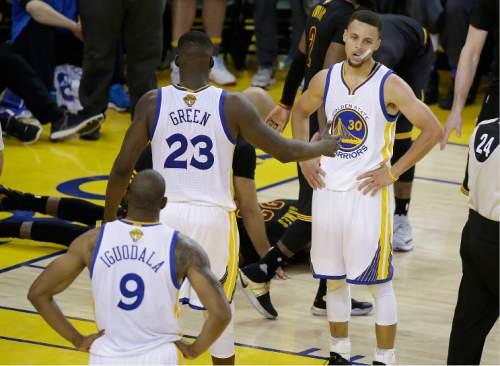 Golden State Warriors guard Stephen Curry (30), forward LeBron James (23) and forward Andre Iguodala (9) stand on the court as Cleveland Cavaliers forward LeBron James, on ground, is tended to during the second half of Game 7 of basketball's NBA Finals in Oakland, Calif., Sunday, June 19, 2016. The Cavaliers won 93-89. (AP Photo/Eric Risberg)