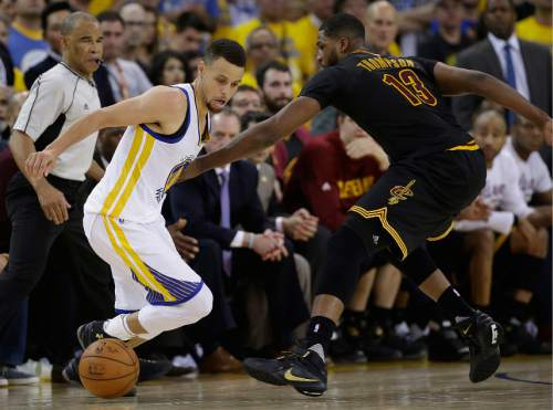 Golden State Warriors guard Stephen Curry, left, dribbles against Cleveland Cavaliers center Tristan Thompson (13) during the second half of Game 7 of basketball's NBA Finals in Oakland, Calif., Sunday, June 19, 2016. (AP Photo/Marcio Jose Sanchez)