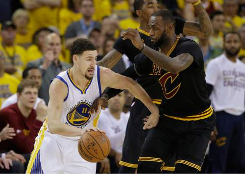 Golden State Warriors guard Klay Thompson (11) dribbles against Cleveland Cavaliers forward LeBron James during the second half of Game 7 of basketball's NBA Finals in Oakland, Calif., Sunday, June 19, 2016. (AP Photo/Marcio Jose Sanchez)