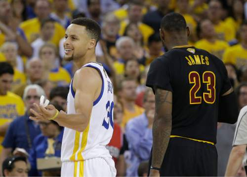 Golden State Warriors guard Stephen Curry, left, reacts next to Cleveland Cavaliers forward LeBron James (23) during the second half of Game 7 of basketball's NBA Finals in Oakland, Calif., Sunday, June 19, 2016. (AP Photo/Marcio Jose Sanchez)