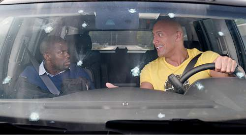 """This image released by Warner Bros. Entertainment shows Kevin Hart, left, and Dwayne Johnson in a scene from, """"Central Intelligence."""" (Claire Folger/Warner Bros. Entertainment Inc. via AP)"""
