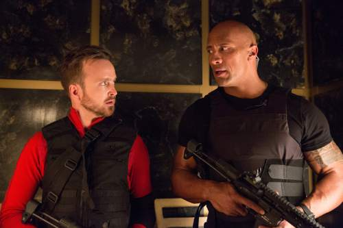 """This image released by Warner Bros. Entertainment shows Aaron Paul, left, and Dwayne Johnson in a scene from, """"Central Intelligence."""" (Claire Folger/Warner Bros. Entertainment Inc. via AP)"""