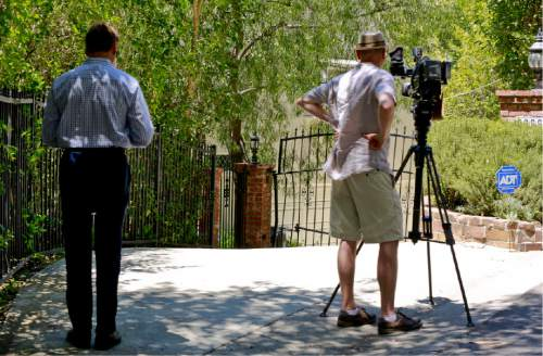 """Television reporters record the driveway to the home of Anton Yelchin, a rising actor, best known for playing Chekov in the new """"Star Trek"""" films, is seen in the Studio City area of Los Angeles, on Sunday, June 19, 2016. Yelchin was killed by his own car as it rolled down his driveway early Sunday, police and his publicist said. The car pinned Yelchin, 27, against a brick mailbox pillar and a security fence at his home in Los Angeles, Officer Jenny Hosier said. He had gotten out of the vehicle momentarily, but police did not say why he was behind it when it started rolling. (AP Photo/Damian Dovarganes)"""