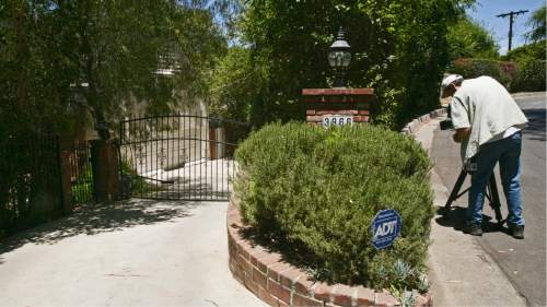 """A Television reporter records the driveway to the home of Anton Yelchin, a rising actor, best known for playing Chekov in the new """"Star Trek"""" films, is seen in the Studio City area of Los Angeles, on Sunday, June 19, 2016. Yelchin was killed by his own car as it rolled down his driveway early Sunday, police and his publicist said. The car pinned Yelchin, 27, against a brick mailbox pillar and a security fence at his home in Los Angeles, Officer Jenny Hosier said. He had gotten out of the vehicle momentarily, but police did not say why he was behind it when it started rolling. (AP Photo/Damian Dovarganes)"""