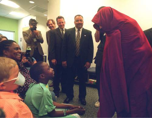 The Dalai Lama shows Brandon Murphy what he can do with his robe when it gets cold while visting the kids at Primary Children's Hospital in 2001. Photo by Rick Egan