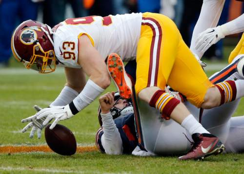 FILE - In this Dec. 13, 2015 file photo, Washington Redskins outside linebacker Trent Murphy (93) recovers a fumble after tackling Chicago Bears quarterback Jay Cutler (6) for a sack during the first half of an NFL football game in Chicago.  NFL teams are trying to cut down on fumbles by practicing with beeping footballs that emphasize ball security. The Redskins, Cowboys, Ravens, Colts and Buccaneers used the footballs during offseason workouts and reported improvement. (AP Photo/Charles Rex Arbogast, file)