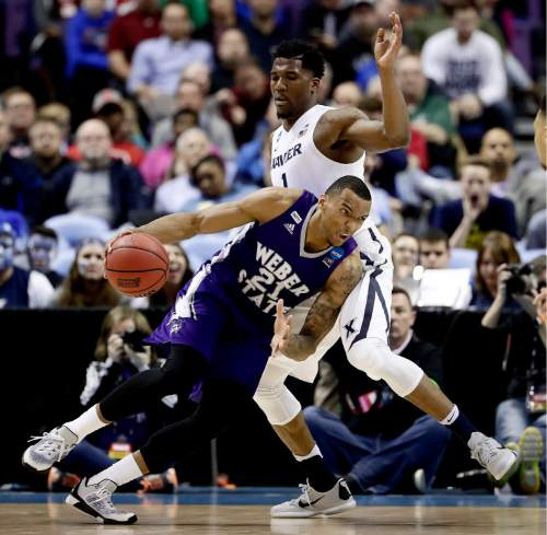 Weber State's Joel Bolomboy (21) moves the ball past Xavier's Jalen Reynolds (1) during the first half of a first-round men's college basketball game in the NCAA Tournament, Friday, March 18, 2016, in St. Louis. (AP Photo/Charlie Riedel)