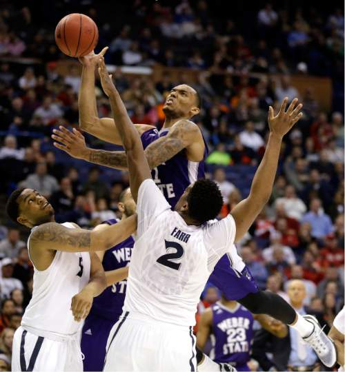 Weber State's Joel Bolomboy, top, heads to the basket as Xavier's Trevon Bluiett, left, and James Farr (2) defend during the first half in a first-round men's college basketball game in the NCAA tournament, Friday, March 18, 2016, in St. Louis. (AP Photo/Jeff Roberson)