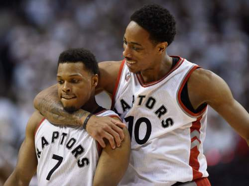 Toronto Raptors' DeMar DeRozan, right, and Kyle Lowry celebrate during the second half of Game 7 of the NBA basketball Eastern Conference semifinals against the Miami Heat in Toronto, Sunday, May 15, 2016. (Frank Gunn/The Canadian Press via AP) MANDATORY CREDIT