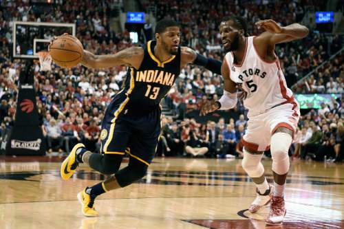 Indiana Pacers' Paul George (13) drives to the basket as Toronto Raptors' DeMarre Carroll (5) defends during the second half of Game 5 of an NBA first-round playoff basketball series, Tuesday, April 26, 2016 in Toronto. (Frank Gunn/The Canadian Press via AP) MANDATORY CREDIT