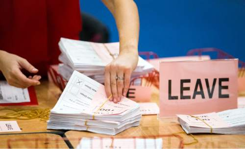 "A teller counts ballot papers at the Titanic Exhibition Centre in Belfast, Northern Ireland, after polls closed in the EU referendum Thursday, June 23, 2016. Britain's referendum on whether to leave the European Union was too close to call early Friday, with increasingly mixed signals challenging earlier indications that ""remain"" had won a narrow victory. (Liam McBurney/PA via AP) UNITED KINGDOM OUT NO SALES NO ARCHIVE"