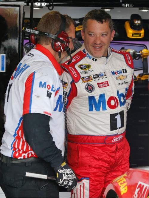 Tony Stewart, right, jokes with a crew member during practice for Sunday's NASCAR Sprint Cup auto race at Richmond International Raceway in Richmond, Va., Friday, April 22, 2016. Stewart is making his return to Sprint Cup racing after a preseason injury. (AP Photo/Steve Helber)