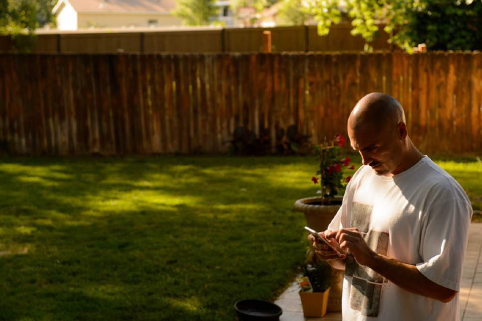 Trent Nelson  |  The Salt Lake Tribune Weldon Angelos is immersed in his new smartphone after serving more than 12 years in prison on federal gun and drug charges. Angelos has been spending time with his family and wants to give talks to at-risk youth about his story. Angelos was released on May 31 after his 55-year mandatory sentence was reduced. Angelos was photographed at his home in Sandy, Thursday June 16, 2016.