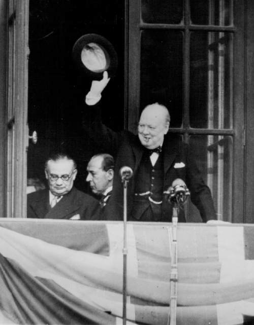 May 12, 1945 Churchill Waves to VE Day Celebrants - Premier Winston Churchill, smoking a customary cigar, waves his hat from the balcony of the Ministry of health building in London, to VE Day celebrants, who surges into Whitehall May 8, in acknowledgement of their cheers. At extreme left is Minister of Lador Ernest Bevin with Sir John Anderson in center.  Associated Press Photo