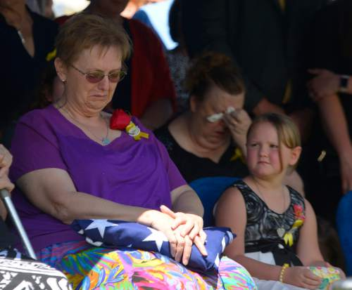 Leah Hogsten  |  The Salt Lake Tribune Oakley Ricks looks at her grandmother Lorie Ricks who sits at her husband's graveside, Utah Transit Authority electrician Kay Ricks, 63, who was laid to rest Saturday, May 28 at Lehi City Cemetery. Ricks served in the Navy and was a veteran of the Vietnam War, 4 years active duty and 2 years in the Naval Reserve and 8 years in the Utah National Guard. Utah police continue gathering evidence that could link two men who fled to Wyoming, after tying up and assaulting a mother and her four teenage daughters in a Centerville home on May 10, to the slaying of Ricks employee whose body was found in rural Wyoming.