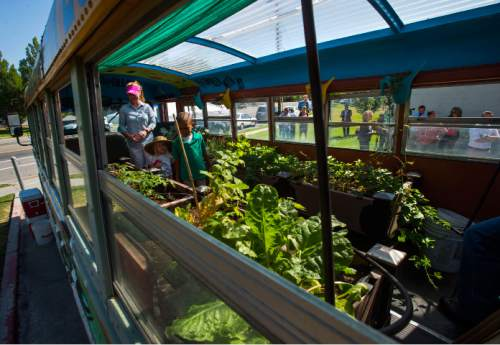 Steve Griffin / The Salt Lake Tribune  People walk through a bus filled with produce after Mayor Jackie Biskupski and others launched a new mobile farmers market for Glendale and Poplar Grove neighborhoods at the Sorenson Unity Center in Salt Lake City Monday June 27, 2016. The market is designed to help some west side communities access more affordable and healthy food.
