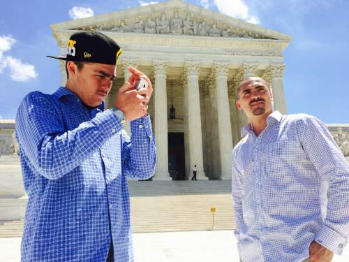 Thomas Burr     The Salt Lake Tribune Weldon Angelos, right, looks on while his son Jesse checks out pictures on his phone outside the Supreme Court building in Washington. Angelos is a Utahn recently released from prison who has become the poster child for criminal justice reform.