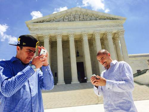 Thomas Burr     The Salt Lake Tribune  Weldon Angelos, right, and his son Jesse check out pictures on their phones outside the Supreme Court building in Washington. Angelos is a Utahn recently released from prison who has become the poster child for criminal justice reform.