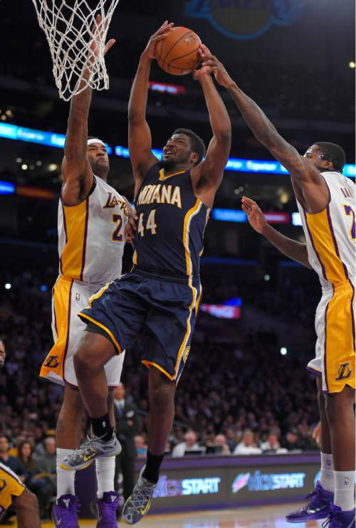 Indiana Pacers forward Solomon Hill, center, goes up for a shot as Los Angeles Lakers center Jordan Hill, left, and forward Ed Davis defends during the first half of an NBA basketball game, Sunday, Jan. 4, 2015, in Los Angeles. (AP Photo/Mark J. Terrill)