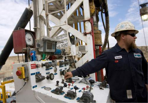|  Tribune File Photo  Jonathan Varelman mans the controls on a super single oil rig's drilling platform  in the Newfield Exploration Company's oil fields in Monument Butte near Roosevelt, Utah on August 9, 2012.