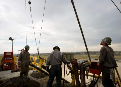 |  Tribune File Photo  Floorhands work on the on the drilling platform of the 68 Pioneer Rig, a telescoping rig, in Newfield Exploration Company's oil fields in the Central Basin near Roosevelt, Utah on August 9, 2012.