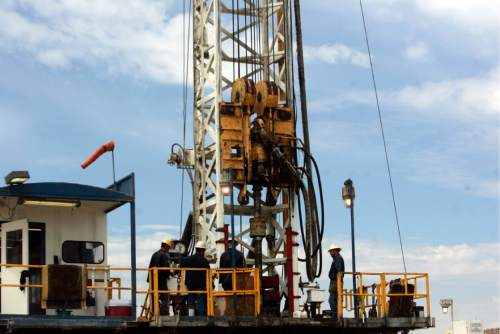 |  Tribune File Photo  Floorhands work on the platform of 68 Pioneer Rig, a telescoping rig, in Newfield Exploration Company's oil fields in the Central Basin near Roosevelt, Utah on August 9, 2012.